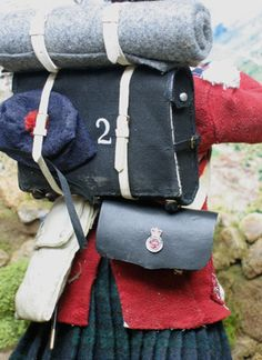 This rear view shows the canvas knapsack with the blanket rolled on top and undress bonnet stuffed into the straps , and the unique badge worn on the 60-round pouch.  Under campaign conditions much of this finery had to be abandoned , and Highland soldiers often had to wear trousers and leave their feathers in store .  On the right you can clearly see the construction of the bonnet : a knitted porkpie , mounted with feathers , a diced band ,a cockade with the red hackle, and a peak.