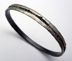 "Todd Pownell: , Bracelet in 950 palladium over oxidized sterling silver with inverted black diamonds. 7mm wide. 2.5"" in diameter."