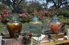 beverage dispensers on rustic soda boxes and herbs tucked in on the table...mason jars lined up on the backside and striped paper straws