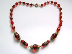 Necklace of bright red Czech glass, with ornate bead caps and filigree tube spacers. C. 1930s.