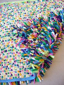 T-Shirt Rug. This rug was created from old T-shirts and burlap. The t-shirts were cut into thin strips, that were then woven into the burlap. There are approximately 1700 of these 1/2 inch by 3 inch strips. They were woven in at random. The rug edges were finished with the T-shirt hems. Created by Meagan Pickett