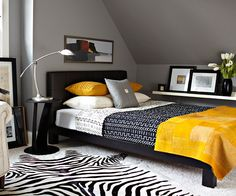 dark room w bright yellow accent color. repitition of black and white patterned prints + solid yellow blanket and pillows. switch out yellow accents when tired w color scheme and choose a new accent