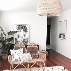 Chic boho coastal home tour. Rattan furniture with textured cushions and coastal artwork