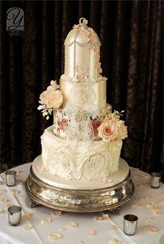 Vintage themed artsy wedding cake..If you want a cake that's dressed up to the nines then you'll love this four tiered cake from Unique Cakes by Yevnig! The craftsmanship and detail is stunning and we especially love the gold birdcage style top tier that's set off with mini flowers.