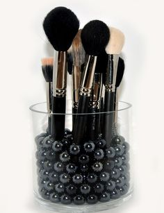 Use an acrylic jar filled with marbles to store brushes upright
