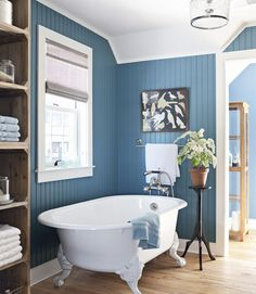 A white clawfoot tub in a blue bathroom. The walls of this blue bathroom (which happens to be from our 2010 eco-friendly House of the Year!) are Benjamin Moore Natura in Fiji. Bad Inspiration, Bathroom Inspiration, Bathroom Ideas, Bathroom Photos, Budget Bathroom, Painting Bathroom Walls, Painting Wood Paneling, Room Paint, Blue White Bathrooms