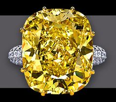 38.86 ct Fancy Intense Yellow  Cushion Cut VS 2 diamond in a hand made  ring with Cushion Cut Diamond set in  18 kt yellow gold engraved basket with  over 150 fully faceted round brilliant  diamonds of top color and finest purity  set in the platinum shank