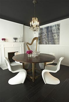 Chic, eclectic dining room with black painted ceiling, fireplace, white Panton Chairs, round salvaged wood dining table and harp. Dark Ceiling, Colored Ceiling, Ceiling Color, Ceiling Lights, Black Walls, White Walls, White Doors, Panton Chair, Boutique Interior Design