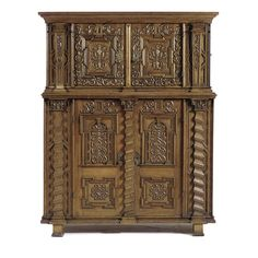 A SOUTH GERMAN OAK CUPBOARD LATE RENAISSANCE, 17TH CENTURY in two sections, the upper section with a pair of panelled doors, carved with scrolls and flanked by pilasters, the side handles of wrought-iron, the lower section en suite to the upper part, doors enclosing a plain interior, on block feet