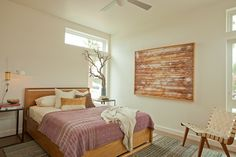 Contemporary bedroom with warm wood details and soft lavendar throw.