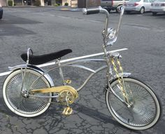 Lowrider Bike with chrome and gold parts, flared rear krate style fender, 140 spoke wheels, and a bullet light.