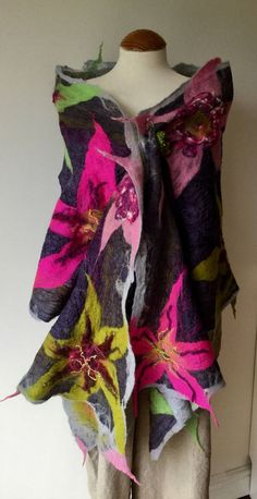 This is a MADE TO ORDER reversible two sided shawl with a base of finest quality silk. The photos show two versions of the same style. On the top side is a felted pattern of dramatic green and pink lily flowers. The other side is a more abstract pattern framed with pale grey edge and some of the green and deep pink colours from the top side and with a centre panel of purple and grey. It measures approx 58cm wide by 194cm long and has undulating edges with some spiky tassles. As This shawl is…