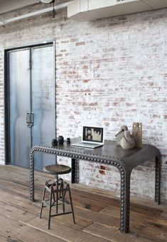 Amazing industrial desk against an exposed brick wall.