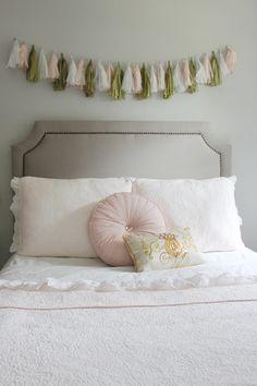 Sweet, yet chic big girl room - love tassel garland over the nailhead headboard!