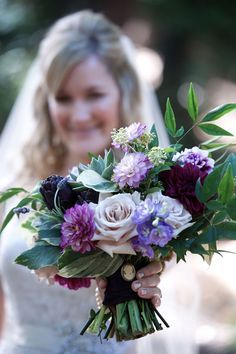 Bridal bouquet with shades of purple...roses, dahlias, a cameo, and even artichokes make this unique. Desmond Charles Photography.
