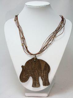 Collar medio de cordón de cuero con piezas metálicas doradas y pieza principal de madera en forma de elefante, grabada.