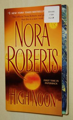 "This is a preowned paperback copy of the romantic suspense novel by Nora Roberts called High Noon. - Status - Used, - Condition - good, - Size - 1-1/8"" x 4-1/4"" x 6-3/4"", - Material - paperback"