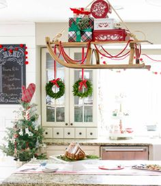 Vintage sled with presents hung over island in farmhouse style kitchen as Christmas decor