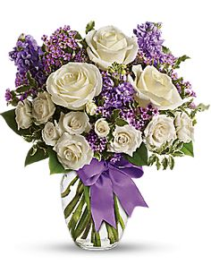 white roses and purple stock mix with delicate lavender waxflower and green pitta negra