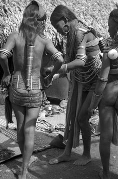 "India | Girls of the Ang clan dressed for dancing. Preparation for O-ya-bu or Spring festival. The Konyak are ruled by chiefs called Ang"" that belong to the ""Ang"" clan. Longkhai, Nagaland, Mon District. 1937. 