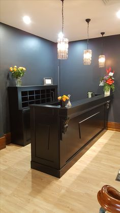 Black retro style reception desk with pigeon holes behind