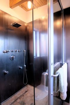 salvaged titanium impregnated elevator panels and commercial entry door were used to make this shower enclosure!