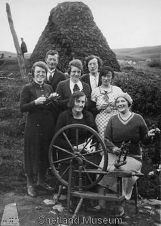 "Shetland Knitting Group, 1930's.   Group knitting and spinning at Voe. The spinning wheel is an unusual variant of a ""Norwa' wheel""."