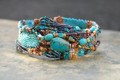 Just picture a lovely stream, the water flowing and glimmering over the colorful rocks beneath. This freeform peyote bracelet is made up of beautiful turquoise and copper beads. Hints of yellow, purple, blue, green, and peach are included in this lovely display of color. Depending on your neck size, this piece could also be worn as a choker. It is 15 in length, the widest point is in the center at 1.5. Large turquoise button with beaded loop as the closure.