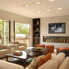Nicole Sassaman - living rooms - modern, fireplace, ivory, modern, couches, sofas, chairs, wood, square, coffee tables, orange, square, ottomans, orange, silk, pillows, cushions, gray, modern, chaise, lounge, green, throw pillow, beige walls, bi-fold, doors, living room, TV over fireplace,