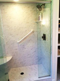 Walk-in shower with glass door, Daltile Carrara ceramic wall and floor tile & Delta shower accessories.