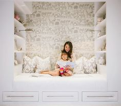 Amazing kid's reading nook features a built-in daybed with three drawers flanked by built-in bookcases illuminated by polished nickel sconces alongside walls clad in Vintage Hand Painted Jungle Animals Wallpaper - Parchment.