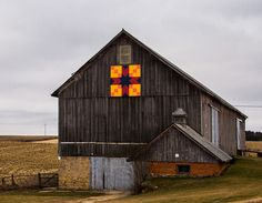 """Brightly colored barn quilt on weathered barn in Green County, Wisconsin. This quilt pattern is named """"Arrow Head"""" by the owners. This pattern was first published in the Kansas City Star in 1931 as Stepping Stones. Original title was Good Cheer in 1906, but has also been known as Arrow Pints, Balck Beauty, Star & Stripe, and the Hunt"""