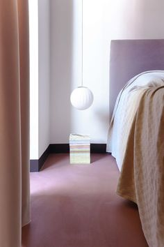 In the bedroom, the floor has a ruddy hue, the result of a brick-red micro cement treatment applied by La Macchina Studio. A low-hanging orb-style pendant light and peach velvet curtains create a softer aesthetic.