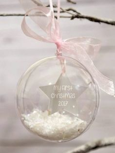 This stunning bauble is made from clear plastic allowing us to customise the interior.  The bauble contains a beautiful engraved pearl white acrylic star and you may choose your own words for example 'My first Christmas 2017' and the name of your choice..  The bauble is then filled with a combination of snow and glittery stars and finished with either baby pink, baby blue or white ribbon.