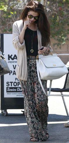 Selena Gomez Black top, beige maxi cardigan, printed maxi skirt, black sandals, white bag, Ray-Ban style sunglasses.