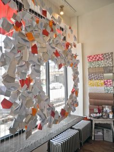 Orange Beautiful Shop (Chicago, IL) window display for Valentines's Day by Sarah Montgomery of Allegory& Image studio (http://allegoryandimage.com/). A rope armature was created from floor to ceiling and envelopes of varying colors where attached to create a free form heart! :)