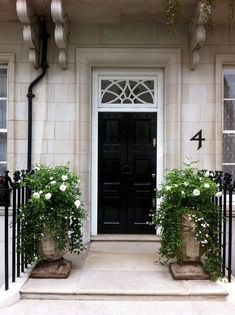 ADORE the black door, the white rose/ivy pots flanking the door are just the right touch