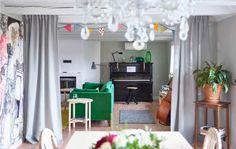 Blick auf ein Familienwohnzimmer mit Sofa und Klavier, der Zugang ist unterbrochen durch einen halb geöffneten Raumteiler aus AINA Meterware in Grau.