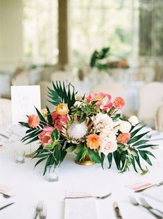 Tropical Coral Wedding Inspiration Tropical wedding centrepiece with palm leaves, protea and peony in coral, orange, pink and yellow Tropical Wedding Centerpieces, Beach Wedding Favors, Wedding Flower Arrangements, Hawaii Wedding, Flower Centerpieces, Wedding Decorations, Centerpiece Ideas, Tropical Weddings, Tropical Wedding Reception