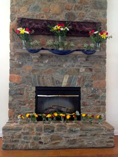 Fireplace used for ceremony alter, decorated with yellow and red flowers