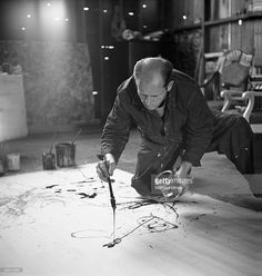 Painter Jackson Pollock working in his studio, dropping paint onto canvas.