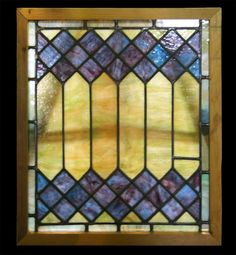 Stained glass window with diamond pattern. Deep blue diamonds contrasts the yellow-green glass that surrounds it in this wonderful stained glass window. $625. 23.5 in. W x 27 in. H x 1.75 in. D, glass 21 in. x 24.25 in.