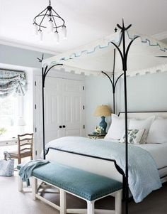Lovely blue gray bedroom design with blue gray walls paint color, black iron Oscar De La Renta canopy bed, White hickory bench upholstered in blue velvet and nailhead trim, turquoise blue lamp, crisp white bedding and baby blue duvet & shams.    Benjamin Moore Pearl Gray