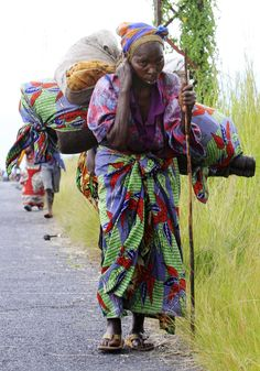 Fleeing the Fighting - A woman flees renewed fighting between the Congolese Revolutionary Army and government army on Nov. 23. An estimated 500,000 people have been displaced by the rebellion since it began in April.