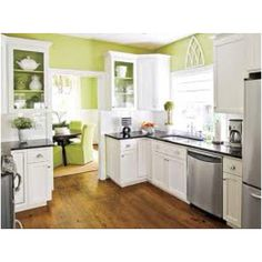 Green kitchen walls, black counter tops, white cabinets