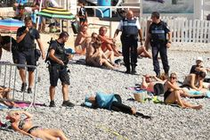 ***URGENT NOTICE - OUR SUPPLIER IS ASKING THAT ALL PUBLICATIONS PLEASE BLUR THE WOMAN'S FACE*** Police fine a woman for wearing a burkini on a beach in Nice. It was staaged