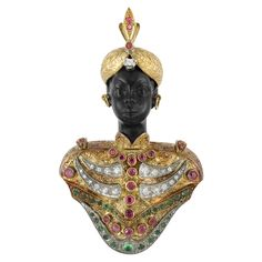 Gold, Silver, Diamond and Gem-Set Blackamoor Clip -  18 kt., the carved blackamoor head wearing a textured gold turban accented by 3 round rubies and one round diamond, with gold hoop earrings, his engraved gold tunic decorated with 18 round and single-cut diamonds, 22 round rubies and 24 round emeralds and one round cabochon emerald, approximately 22.3 dwt.