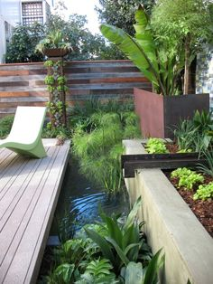 beautiful water feature with a steal beam for a waterfall. interesting way to break up a wood deck with different sized boards.