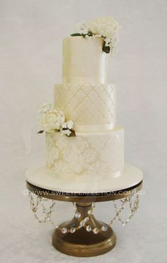 Brushed pale gold/ivory wedding cake with custom sugar flowers and royal icing pattern. Bespoke gold wedding stand with Swarovski crystals.