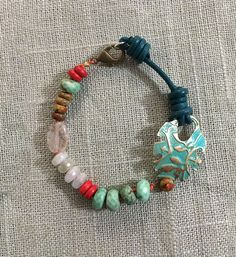 Turquoise Bracelet with Quartz & Red Coral beads, an embossed brass leaf connector with a turquoise patina. Handcrafted on teal leather and orange cotton cord.